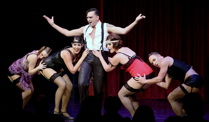 "Emcee (Galloway Stevens) surrounded by Kit Kat Girls (l-r) Lulu (Sierra Wells), Helga (Layli Kayhani), Kost (Leah Kolb) and Bobby (Kerry Lambert) in Oregon Cabaret Theater's production of ""Cabaret""."