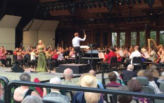 Guest singer Morgan James singing at the microphone and Music Director Teddy Abrams at the podium directing the Britt Orchestra for the performance of Something's Coming from Leonard Bernstein's West Side Story on August 9, 2015 in Jacksonville, OR.
