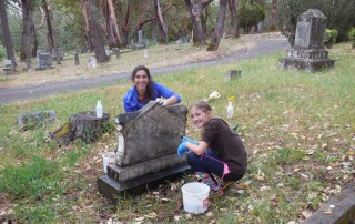 Headstone cleaning by Michele Simmons and her daughter Ruby. Photo by Mary Siedlecki.